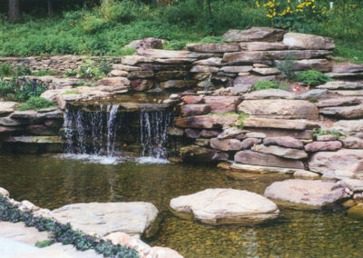 Pond barrier and waterfall with natural boulders