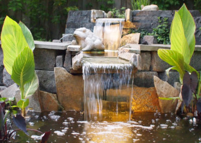 Pond waterfall with large boulders and cut stone.